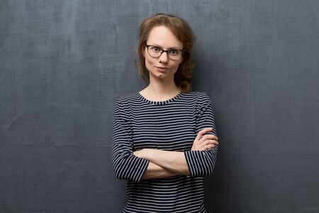 Studio waist-up portrait of dissatisfied caucasian fair-haired young woman with glasses, wearing striped blouse, looking accusingly at camera, holding arms crossed on chest, over gray background Reklamní fotografie