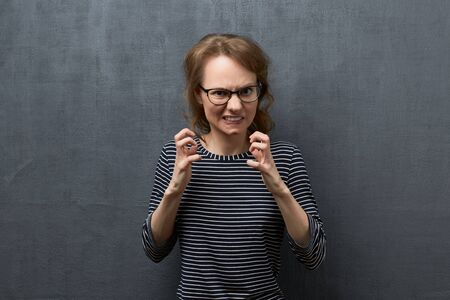 Studio waist-up portrait of furious caucasian fair-haired young woman with glasses, wearing striped blouse, clenching teeth, looking at camera, shaking hands in threaten gesture, over gray background