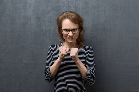 Studio waist-up portrait of furious caucasian fair-haired girl with glasses, wearing striped blouse, clenching teeth, looking at camera, holding fists clenched in front of her, over gray background