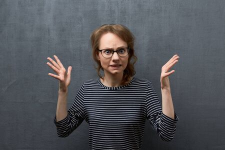 Studio portrait of discontent caucasian fair-haired girl with eyeglasses, frowning face and looking at camera, gesturing with hands trying to explain something while arguing, over gray background