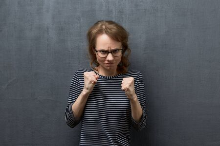 Studio portrait of furious caucasian fair-haired young woman with glasses, clenching teeth, looking at camera, holding fists in front of her ready to fight or defend herself, over gray background