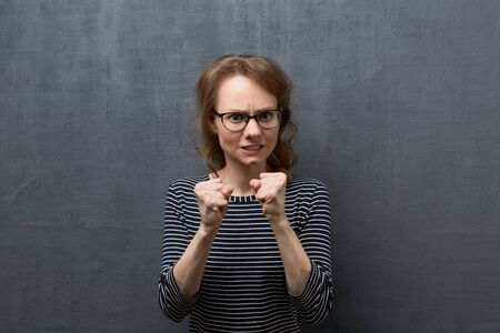 Studio waist-up portrait of angry caucasian fair-haired young woman with glasses, wearing striped blouse, clenching teeth, looking at camera, shaking fists in threaten gesture, over gray background 写真素材