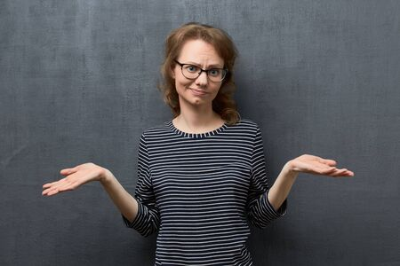 Studio portrait of disappointed caucasian fair-haired young woman with glasses, looking with perplexed expression at camera, raising hands with regret, hearing no arguments, over gray background Imagens