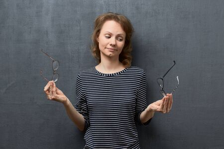 Studio portrait of puzzled caucasian fair-haired young woman, wearing striped blouse, holding glasses with each hands, doubting and trying to choose the best, standing over gray background Фото со стока