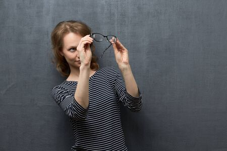 Studio portrait of cute caucasian fair-haired girl, wearing striped blouse, holding glasses with hands and looking with interest through them, trying to discern something, over gray background