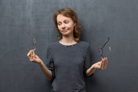 Studio portrait of puzzled caucasian fair-haired girl, wearing striped blouse, holding glasses with each hands, doubting and trying to choose the best, standing over gray background