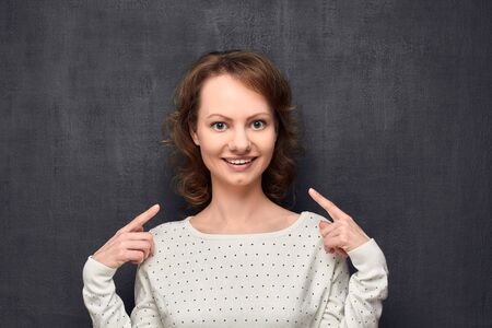 Studio close-up portrait of cute caucasian fair-haired girl, wearing light-colored blouse, pointing with index fingers at herself, smiling broadly and looking at camera, standing over gray background