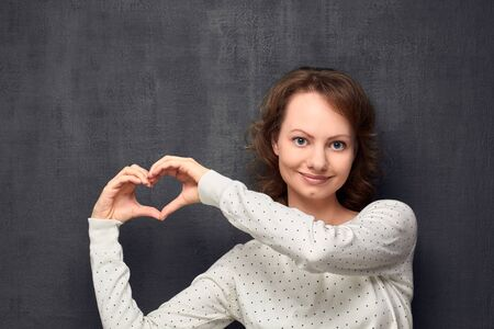 Studio portrait of cheerful caucasian fair-haired girl, wearing light-colored blouse, making heart gesture near head, smiling and looking at camera, over gray background, love concept