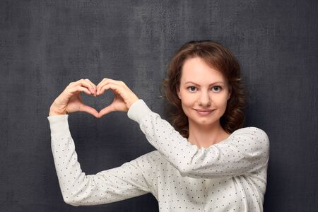 Studio portrait of cheerful caucasian fair-haired young woman, wearing light-colored blouse, showing heart with hands near head, smiling and looking at camera, over gray background, love concept Banco de Imagens