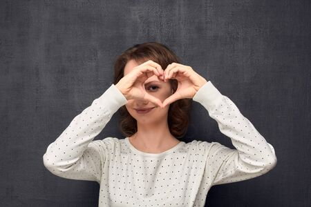 Studio portrait of cheerful caucasian fair-haired girl, wearing light-colored blouse, making heart gesture near head, smiling and looking through heart, standing over gray background, love concept