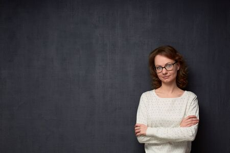 Studio waist-up portrait of confident caucasian fair-haired young woman with glasses, wearing sweater, looking calmly at camera, holding arms folded, against gray background, copy space on left