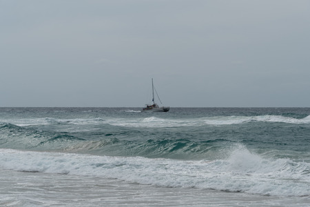 Sailboat off the coast of Kauai's remote beach at the edge of the Napali Coast in winter