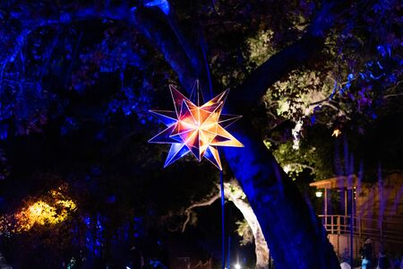 Enchanted: Forest of Light - shiny illuminated mirror star suspended in midair