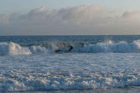 Surfing at Zuma Beach at sunset at high tide, Malibu, Southern California