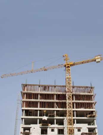 Construction of building with the help of highrise crane Stock Photo - 14513182