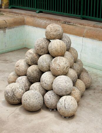 Stacked ancient Canon balls made of granite rock Stock Photo