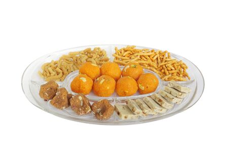 Different types of Indian sweets and snacks kept in a plate