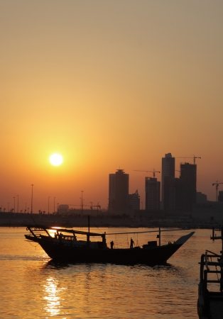 Dhow moving out to the sea during sunset photo