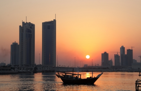 Dhow and Seef skyline during sunset in Bahrain