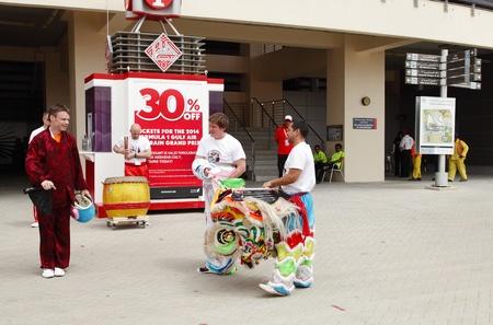 entertaining area: SHAKIR, BAHRAIN - APRIL 19: Chinese Lion Dance troupe entertaining people at Formula 1 village, vending area & entertainment in 2013 Formula 1 Gulf Air Bahrain Grand Prix on April 19, 2013 in Shakir, Bahrain