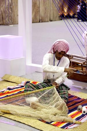 folk tales: SANABIS, BAHRAIN - MAY 04  An expert generates fishing net during 20th Heritage festival  Folk Tales  Sea, Land and City  2012 in Sanabis, Bahrain on May 04, 2012