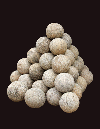 artillery shell: Stacked ancient Canon balls made of granite rock isolated on black