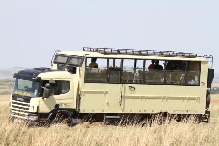 game drive: MASAI MARA, KENYA-OCTOBER 20  A Safari bus in the grassland of Masai Mara for game drive in Masai Mara National Reserve  National Park  on October 20, 2013 in Masai Mara, Kenya, Africa