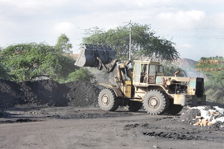 A payloader piling coal to load on dumper photo