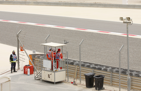 facilitate: SHAKIR, BAHRAIN - APRIL 04  Marshal standing alert to facilitate the race during practice session on Friday, April 04, 2014, Formula 1 Gulf Air Bahrain Grand Prix 2014 Editorial