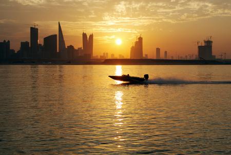 A speeding boat against bahrain skyline during sunset Stock Photo