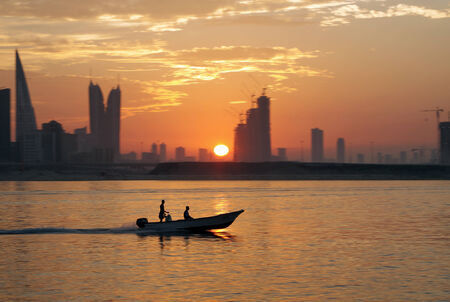 A boat during sunset with Bahrain highrise buildings photo