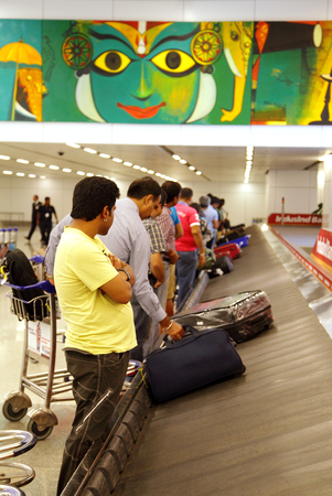 identifying: DELHI AIRPORT, INDIA- AUGUST 16: Passengers identifying their baggages on carousel at Delhi Airport on August 16, 2013, Delhi, India Editorial