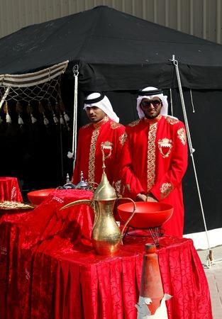 traditional dress: SAKHIR AIRBASE, BAHRAIN - JANUARY 16: Arabic men in traditional dress serving traditional coffee Qehwa in Bahrain International Airshow at Sakhir Airbase, Bahrain on 16 January, 2014