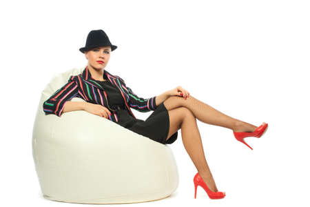 Woman motley jacket hat shoes sitting bale photo