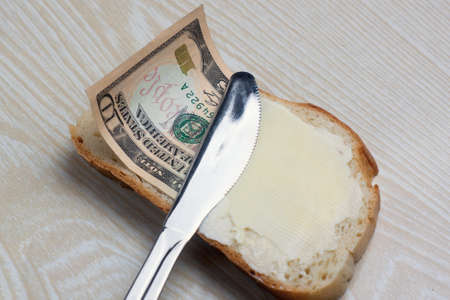 butter and money on a slice of bread and knife Stock Photo