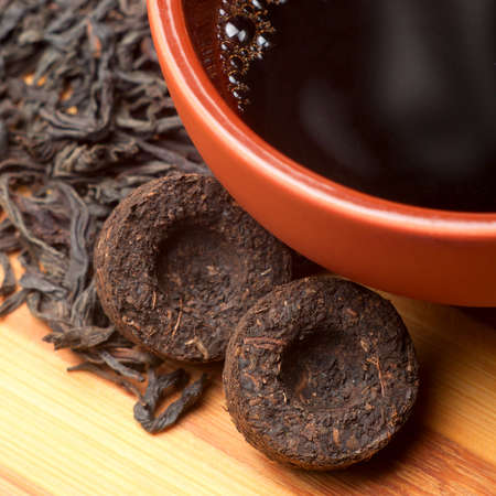 The cup of pu-erh and two bricks of old pu-erh tea