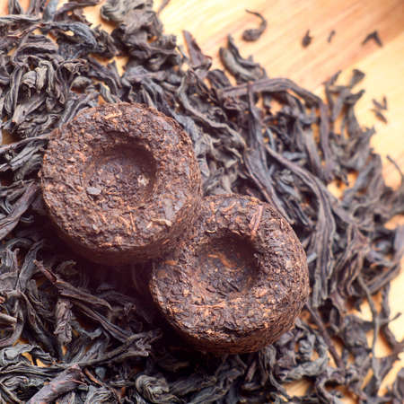 Two bricks of old aroma tea pu-erh on dry tea background photo