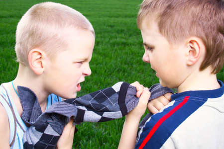 Children fighting over a sweater on a green field photo