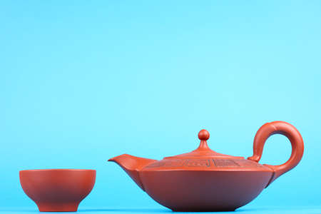 Arabian old ceramic brown teapot with teacups isolated on blue photo