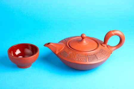 Arabian old ceramic brown teapot with teacups isolated on blue Stock Photo - 13404774