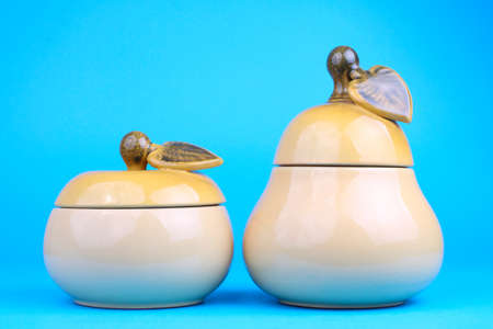 Two sugar-bowls in the form of a pear and apple isolated on blue background Stock Photo - 13404773