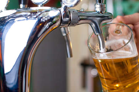 Draft beer pour in a glass from the crane Stock Photo