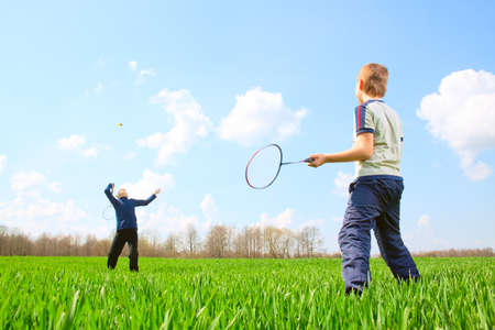 Family - two little boys playing badminton on green meadow