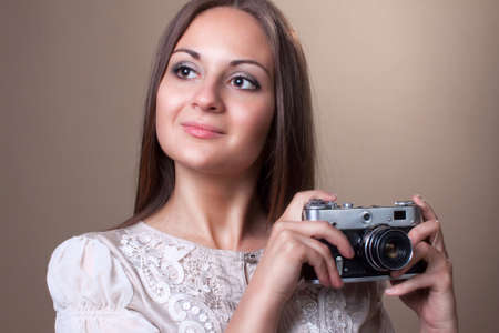 Portrait of a cheerful young girl with old camera photo