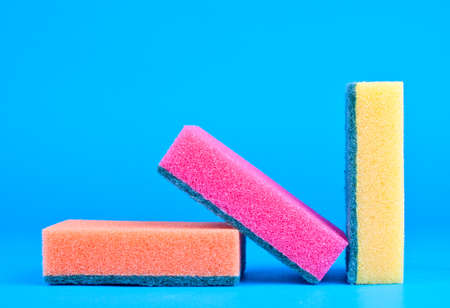 Three kitchen sponges colored on blue background photo