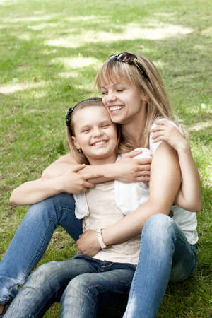 Cute mother and daughter on meadow in park photo