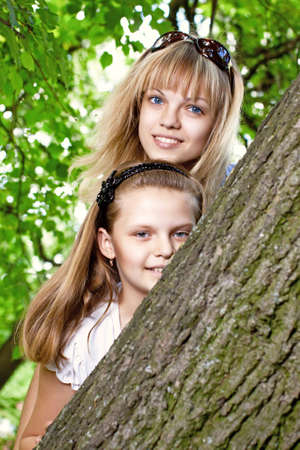 Cute mother and daughter looking out over the tree photo