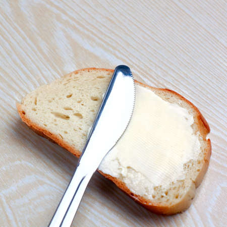 butter on a slice of bread and knife