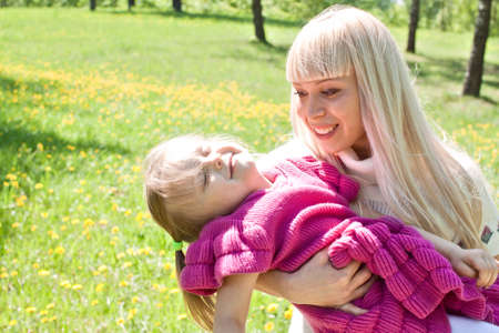 Happy young mother with sleeping girl on hands in summer park photo