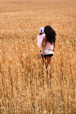 mother and daughter walking out in a wheat field photo